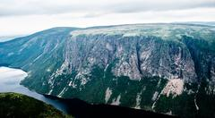 Large steep cliffs and plateau forming fjord under overcast sky - stock photo
