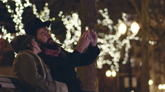 Classy couple take selfy on bench in park decorated with holiday lights at night Stock Footage