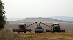 Harvesters unload grain into trailer Stock Footage