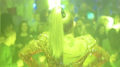 Back side of blonde go go dancer in glowing suit on stage of crowded nightclub - stock footage