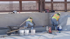 Two Construction Workers Finish Concrete Work Stock Footage