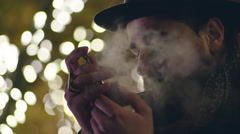Portrait of a young gentleman smoking a pipe with holiday lights in background Stock Footage