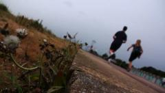 Tilted Shot Pathway Joggers Running Verge Weeds Road Exercising Beach Stock Footage