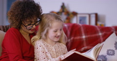4K Babysitter & little girl reading together at home Stock Footage