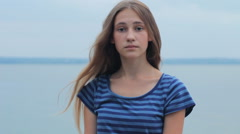 Beautiful thoughtful girl on the river shore looking at camera Stock Footage