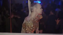 Back side of go go dancer in glowing suit on stage of nightclub. Slow motion Stock Footage
