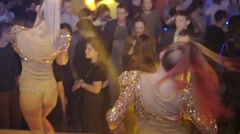 Back side of go go dancers in glowing suits on stage of nightclub. Slow motion - stock footage