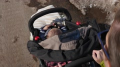 High shot mother pushing baby in stroller - stock footage