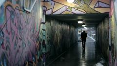 Man walks down graffiti covered underpass evening Stock Footage