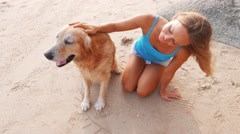 Happy looking mature woman is enjoying a sunset at the beach with her pet dog Stock Footage