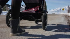 Low shot mother pushing baby in stroller - stock footage
