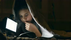 Girl night reading book under covers with flashlight Stock Footage