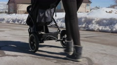 Mother walking her baby boy in stroller on road - stock footage