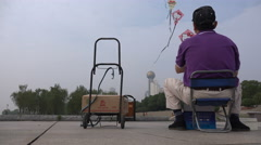 A senior Chinese man lets up a colorful kite in the city of Wuhan Stock Footage