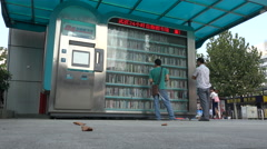 Students lend books at automatic vending machine near Wuhan university, China Stock Footage