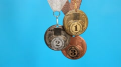 Gold, silver, bronze medal on a blue Stock Footage