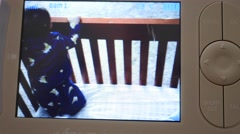 Watching a baby playing in his crib on a monitor Stock Footage
