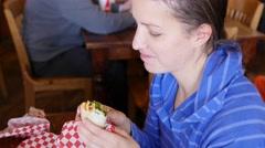 Woman eating her sandwich wrap in a sandwich shop Stock Footage
