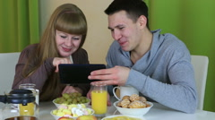 Young cheerful couple in love looking at tablet and talking over breakfast Arkistovideo