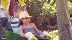 Father holding his children in a wheelbarrow Stock Footage