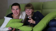 Young couple with glass of wine watching comedy on television and laugh Stock Footage