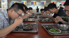 Students eat lunch in a school canteen at the Wuhan University in China - stock footage