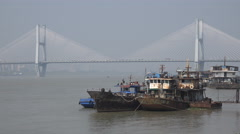 Old rusty vessels contrast, modern suspension bridge, Yantgze, Wuhan, China Stock Footage