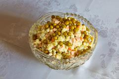 Russian salad with green peas costs on a table - stock photo