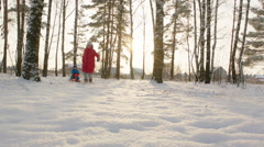 Woman Running and Pulling Toboggan with Little Boy Stock Footage
