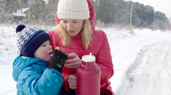 Mother and Son Drinking Hot Beverage from the Thermos Bottle Outdoor Stock Footage