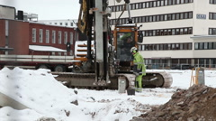 A large machine works at a construction site to knock down piles in the ground Stock Footage
