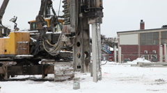 A large machine works at a construction site to knock down piles to the ground Stock Footage