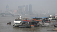 A passenger ferry arrives at the pier, skyline of Wuhan, China Stock Footage