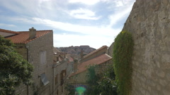 View of stone buildings and plants on a sunny day in Dubrovnik - stock footage
