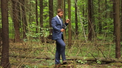 Man in suit shooting video and smoking cigar in the forest Stock Footage