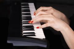 Two woman's hands on synthesizer keyboard Stock Photos