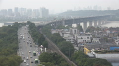 Cargo train and heavy traffic cross bridge in Wuhan, China Stock Footage