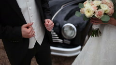 bride with a bouquet and groom near a retro car - stock footage