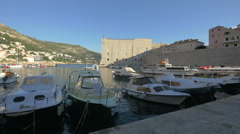 View of moored boats in the port and Saint Ivan fortress in Dubrovnik, Croatia Stock Footage