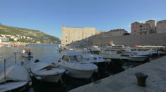 Moored boats and people walking in the port in Dubrovnik Stock Footage