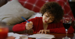 4K Beautiful woman writing christmas cards with a glass of red wine Stock Footage