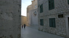 Mother and girl walking on a street and a man standing on a building, Dubrovnik Stock Footage