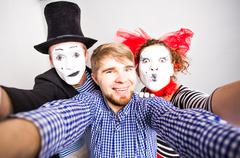 Funny couple of mimes taking a selfie photo,  April Fools Day concept - stock photo