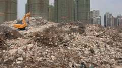 An excavator drives across a demolished quarter in Wuhan, China Stock Footage