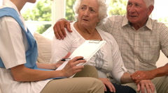Senior couple talking to nurse - stock footage