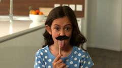 Daughter with fake mustaches making faces Stock Footage