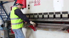 Worker bend metal plate on big machine 2 Stock Footage