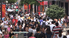 Crowds walk through busy shopping street in weekend, Wuhan, urban China Stock Footage