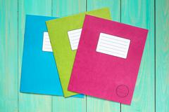 Exercise books on the blue wooden background - stock photo