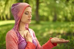 Serene and peaceful woman practicing mindful awareness mindfulness by meditating - stock photo